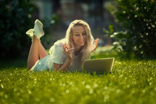 Jonge vrouw met laptop ligt op het gras in het park op een zonnige dag.