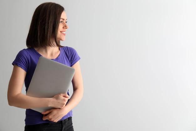 Jonge vrouw met laptop op witte achtergrond