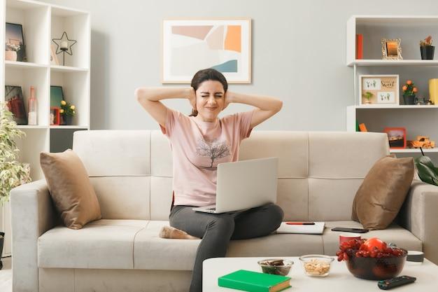 Jonge vrouw met laptop zittend op de bank achter de salontafel in de woonkamer