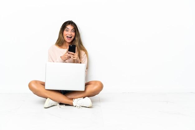 Jonge vrouw met laptop zittend op de vloer geïsoleerd op wit verrast en het verzenden van een bericht