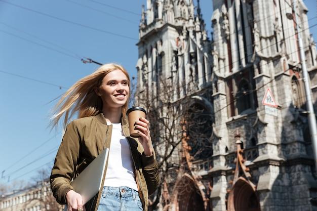 Jonge vrouw met laptopcomputer en koffie wandelen in de straat