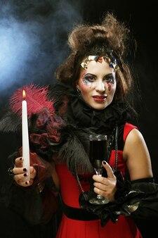 Jonge vrouw met lichte make-up die carnaval-kostuum draagt dat een kaars houdt. halloween foto.