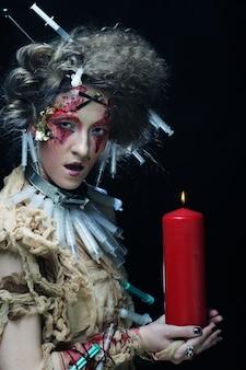 Jonge vrouw met lichte make-up die carnaval-kostuum draagt dat een kaars houdt