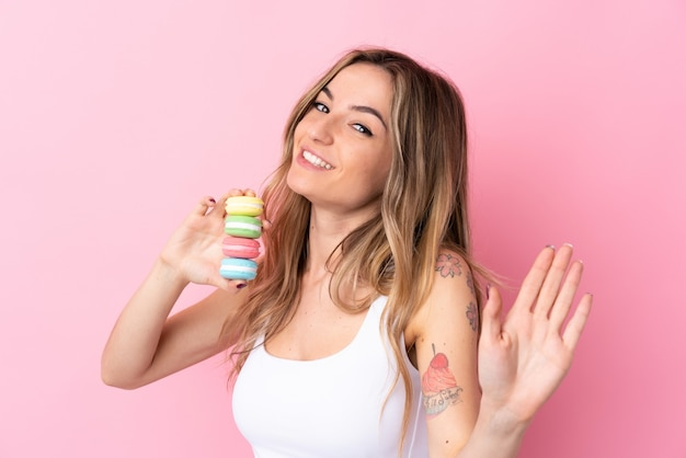 Jonge vrouw met macarons die met hand met gelukkige uitdrukking groeten