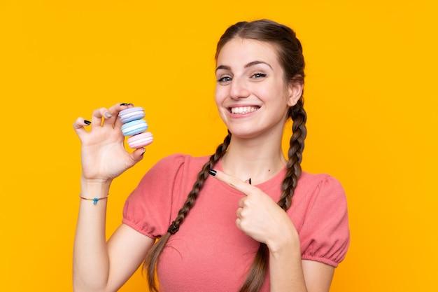 Jonge vrouw met macarons over geïsoleerde muur