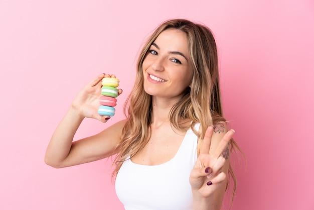 Jonge vrouw met macarons over geïsoleerde roze muur die en overwinningsteken glimlacht toont