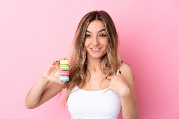 Jonge vrouw met macarons over geïsoleerde roze muur met verrassingsgelaatsuitdrukking