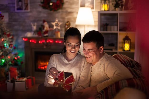 Jonge vrouw met magisch geschenk van man op eerste kerstdag met open haard en kerstboom in donkere woonkamer.