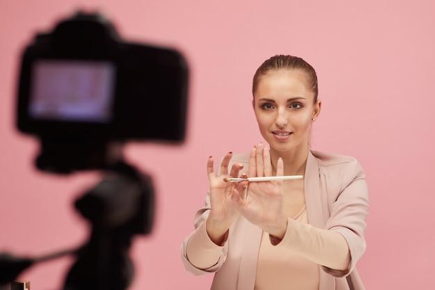 Jonge vrouw met make-up borstel in haar handen en haar volgelingen onderwijzen om make-up op videocamera te doen