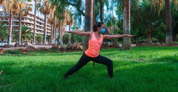 Jonge vrouw met masker die yogahouding doet in het park in het nieuwe normaal