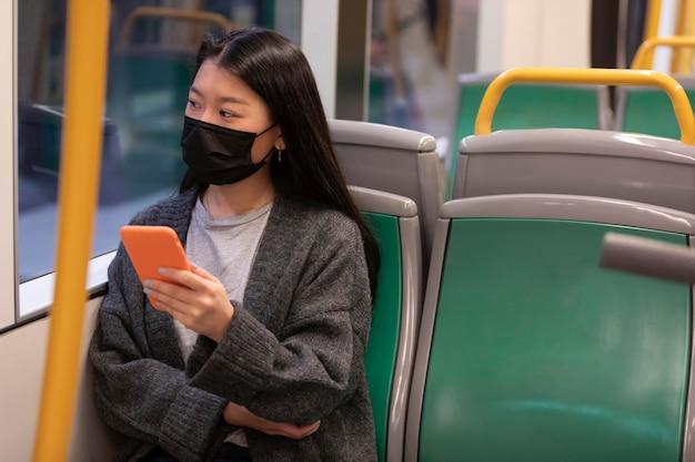 Jonge vrouw met masker in bus