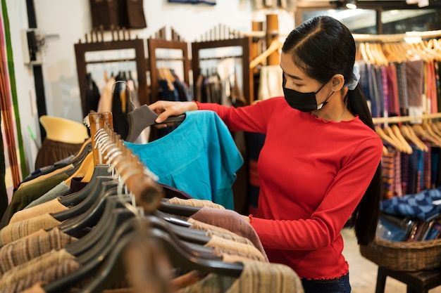 Jonge vrouw met masker in winkel kijken naar jurken