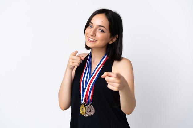 Jonge vrouw met medailles die op witte muur wordt geïsoleerdm wijst vinger naar u met een zelfverzekerde uitdrukking