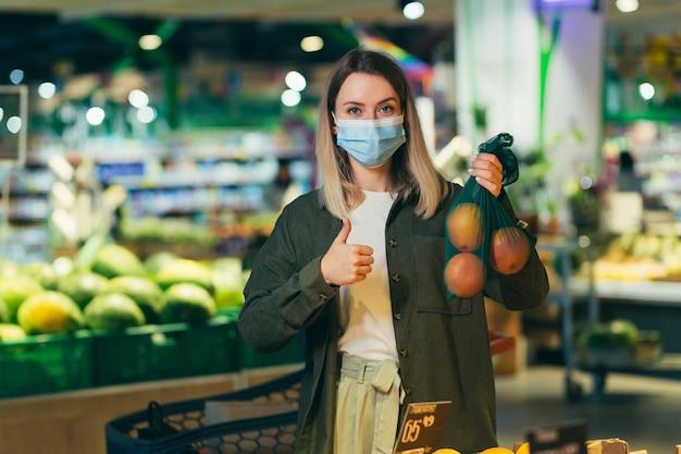 Jonge vrouw met medisch beschermend masker kiest en plukt in eco-zak groenten of fruit in de supermarkt vrouw staat in een supermarkt-markt in de buurt van de toonbank koopt in een herbruikbare verpakking
