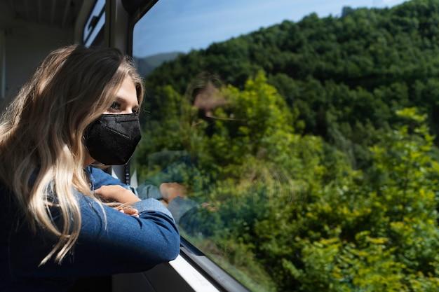 Jonge vrouw met medisch masker die naar een prachtig uitzicht op de natuur kijkt