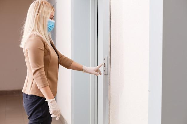 Jonge vrouw met medisch masker in de lift van een flatgebouw