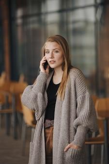 Jonge vrouw met mobiel in café.