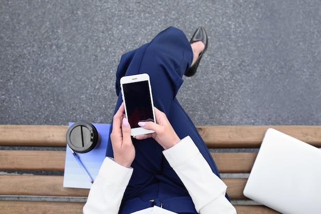 Jonge vrouw met mobiele telefoon die op bank buiten rust