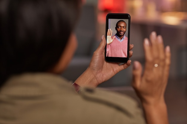 Jonge vrouw met mobiele telefoon en zwaaien naar haar vriendje terwijl ze online met hem praat