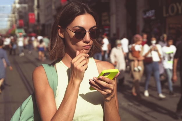 Jonge vrouw met mobiele telefoon reist door de drukke straten van istanboel en geniet van de schoonheid van de stad