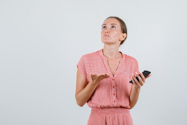 Jonge vrouw met mobiele telefoon terwijl het opzoeken in gestreepte jurk en op zoek verward, vooraanzicht.