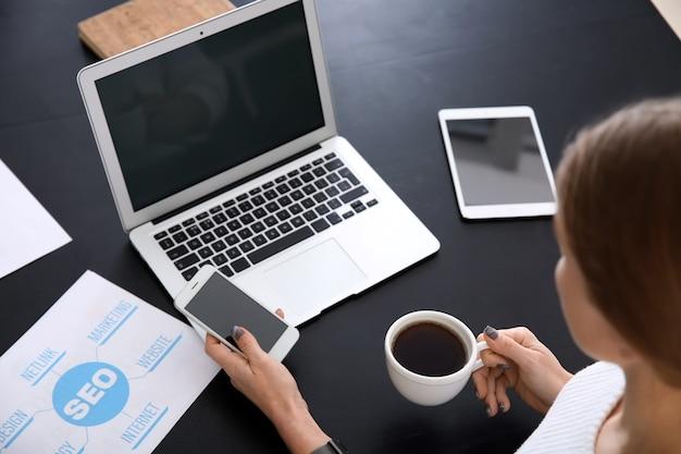 Jonge vrouw met moderne apparaten die in bureau werken