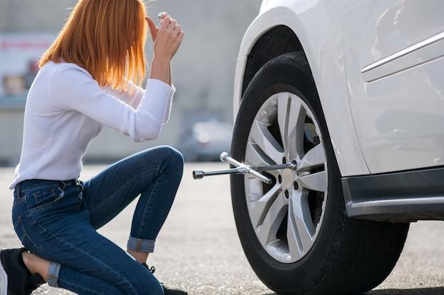 Jonge vrouw met moersleutel veranderend wiel op een gebroken auto.