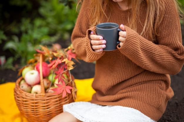 Jonge vrouw met mok hete koffie in een hand