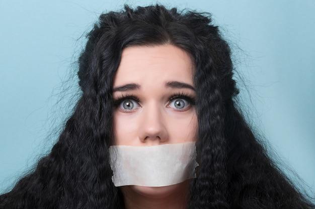 Jonge vrouw met mond en lippen verzegeld in plakband, gecensureerd en verboden om te spreken, gegijzeld
