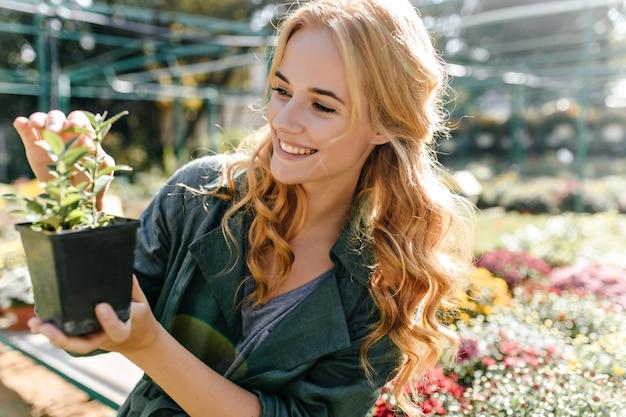 Jonge vrouw met mooi blond haar en zachte glimlach, gekleed in groen gewaad met riem werkt in kas