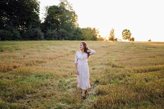 Jonge vrouw met mooi haar poseren in veld bij zonsondergang. mode, onafhankelijkheid