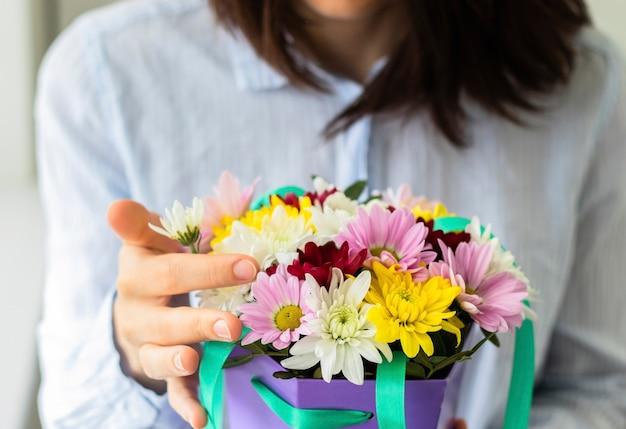 Jonge vrouw met mooi kleurrijk boeket in een doos close-up