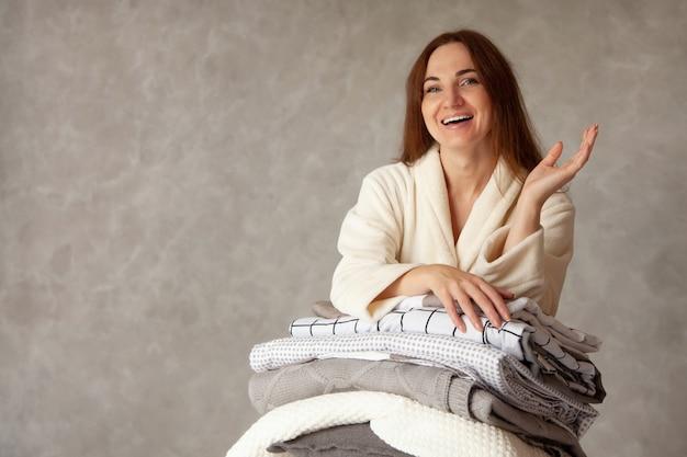 Jonge vrouw met mooie glimlach in warm beige gewaad leunt op stapel gevouwen lakens in verschillende textuur. beddengoed van natuurlijk en biologisch katoen. kopieer ruimte. vervaardiging. hotel industrie.
