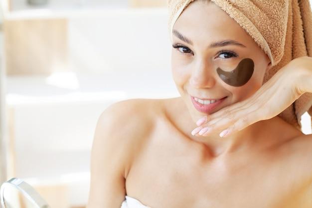 Jonge vrouw met mooie huid legt zwarte vlekken op haar gezicht