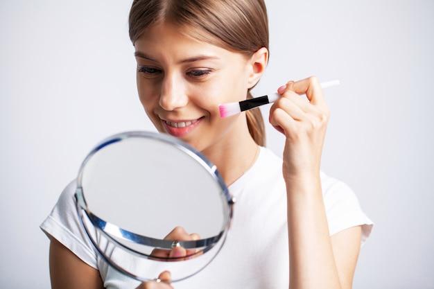 Jonge vrouw met mooie huid zet hydraterende crème op haar gezicht