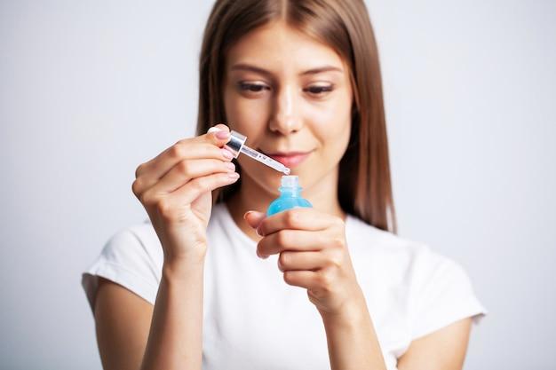 Jonge vrouw met mooie huid zet vitamines op haar gezicht