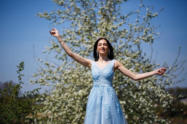 Jonge vrouw met mooie make-up met een vintage hoepel in een blauwe lichte jurk met een boeket poseren op een achtergrond van groen gebladerte in een park. vers portret aantrekkelijk meisje met witte bloemen.