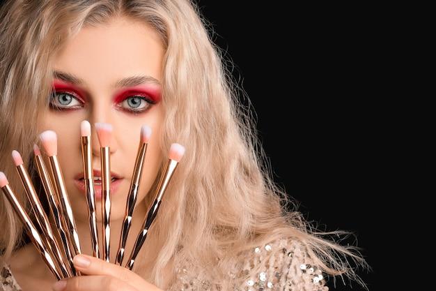 Jonge vrouw met mooie oogschaduw en make-upborstels op dark