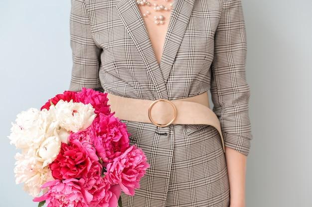 Jonge vrouw met mooie pioenbloemen op grijs