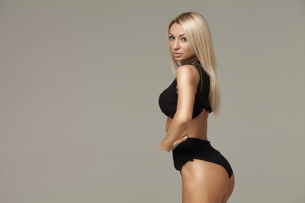 Jonge vrouw met mooie slanke gezonde lichaam poseren in studio. fitness vrouwelijk model in sportkleding op grijze achtergrond