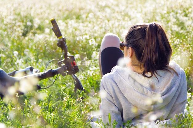 Jonge vrouw met mountainbike uitgestrekt op het veld