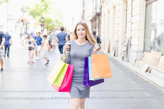 Jonge vrouw met multi gekleurde boodschappentassen lopen op straat