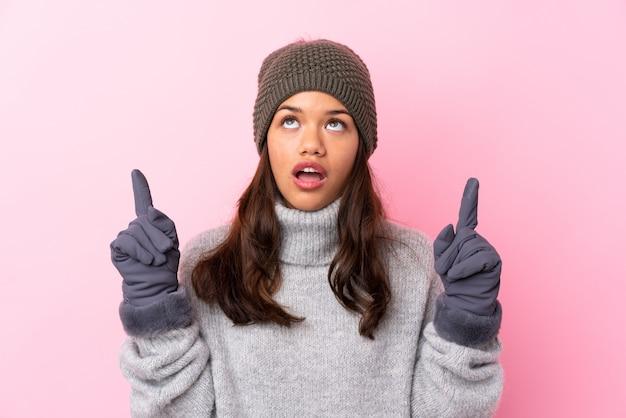 Jonge vrouw met muts over geïsoleerde muur
