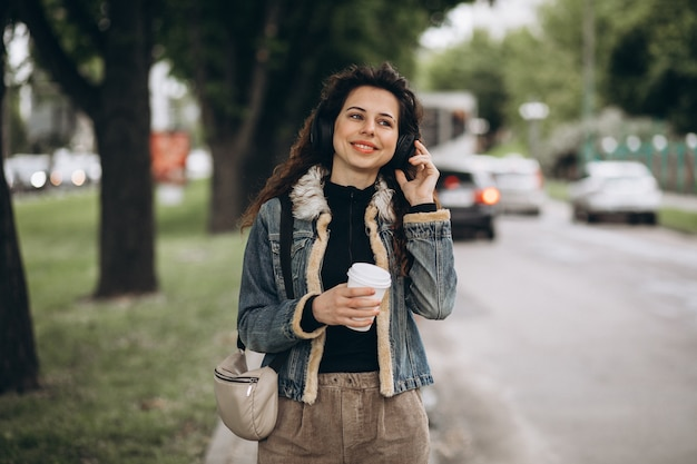 Jonge vrouw met muziek luisteren en koffie drinken
