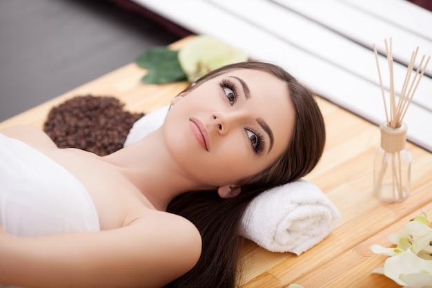 Jonge vrouw met natuurlijk gezichtsmasker in beauty spa
