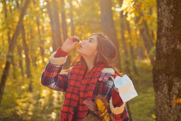 Jonge vrouw met neuswisser dichtbij de herfstboom. portret van jonge vrouw snuiven neusspray sluiten een neusgat. vrouw met allergiesymptomen die neus snuiten.