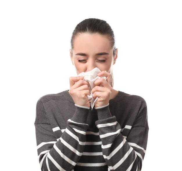 Jonge vrouw met neuswisser op wit. allergie concept