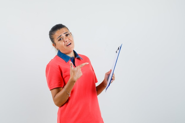 Jonge vrouw met notitieboekje bij de hand en ernaar wijzend met wijsvinger in rood t-shirt en peinzend, vooraanzicht op zoek.