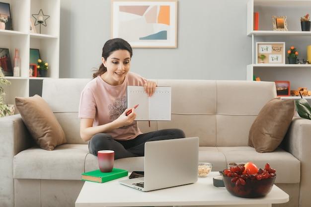 Jonge vrouw met notitieboekje zittend op de bank achter de salontafel en kijkt naar laptop in de woonkamer