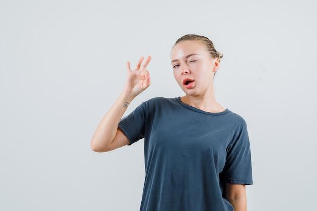 Jonge vrouw met ok gebaar en knipogen oog in grijs t-shirt